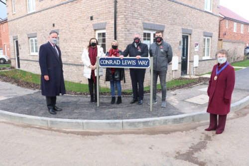 Councillors and the family of Conrad Lewis stood in front of the 'Conrad Lewis Way' road sign