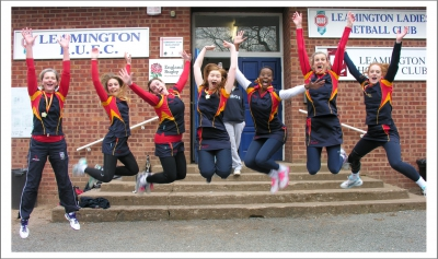 Girls jumping in front of the Leamington Netball Club building